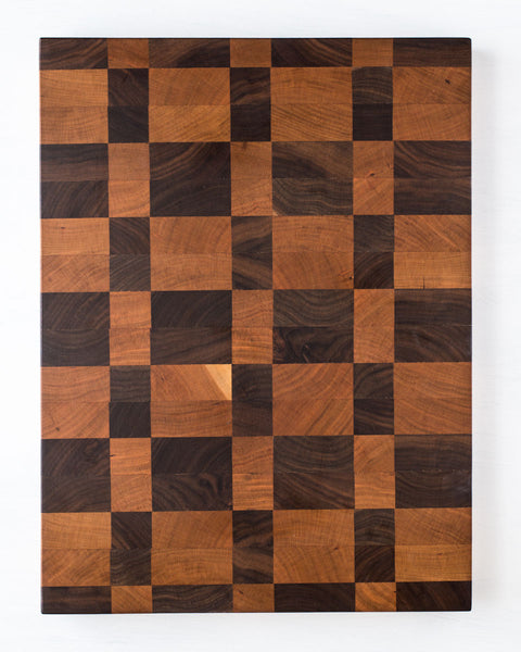 This gorgeous end grain cutting board features a rich and colorful combination of hardwoods that include cherry and walnut in a checkered pattern.
