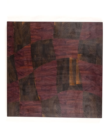 "This end grain cutting board features a rich and colorful combination that includes walnut and purpleheart in a unique ""drunken"" pattern."
