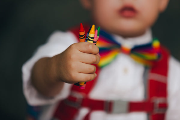 toddler holding handful of crayons