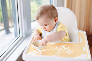Baby/Kid/Toddler eating eggs out of a bowl sitting in an IKEA Antilop high chair with a yellow silicone tray placemat/meal mat with a printed giraffe in an aeroplane flying through clouds.