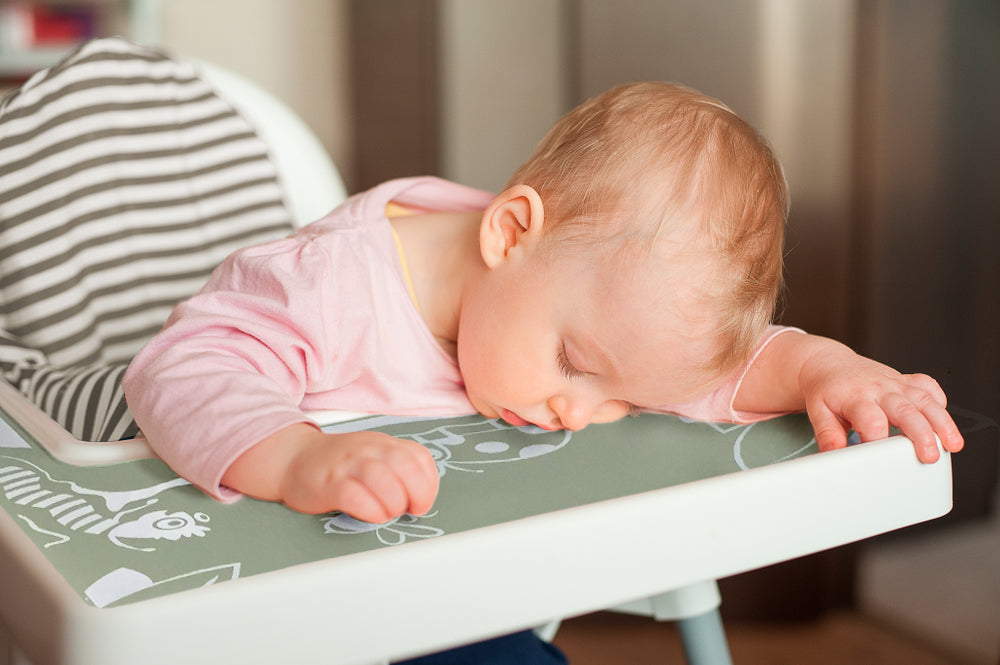 Baby/kid/Toddler sleeping resting head/lying down whilst sitting in IKEA Antilop high chair with a green garden scene silicone placemat/meal mat designed by Toddle Way to fit perfectly on the high chair tray.