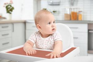 Baby/kid/Toddler sitting in IKEA Antilop high chair with a red silicone placemat/meal mat designed by Toddle Way to fit perfectly on the high chair tray.
