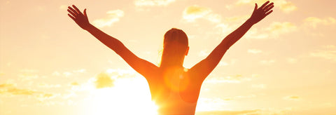 A woman with arms outstretched as she faces and welcomes the sunrise.