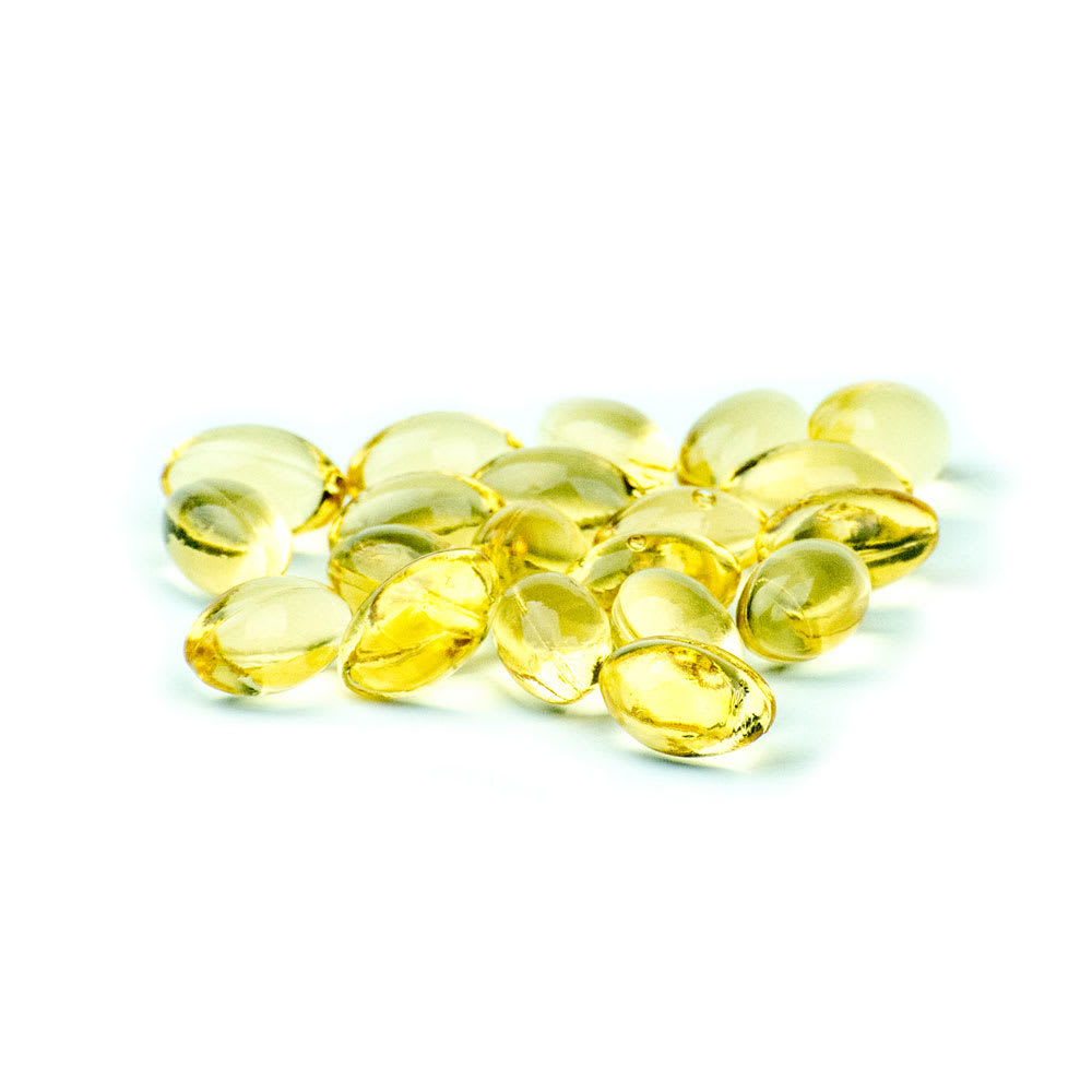 Loose, yellow CBD soft gel capsules on a white background.