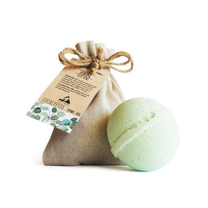 A green Eucalyptus CBD bath bomb next to its hemp cloth bag.