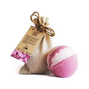 A pink and white Pink Sugar CBD bath bomb sitting next to its hemp cloth bag.