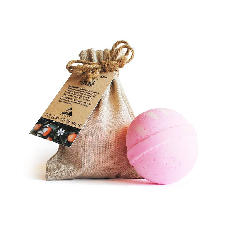 A Tangerine Dream CBD bath bomb by Topikal sitting outside its hemp cloth bag.