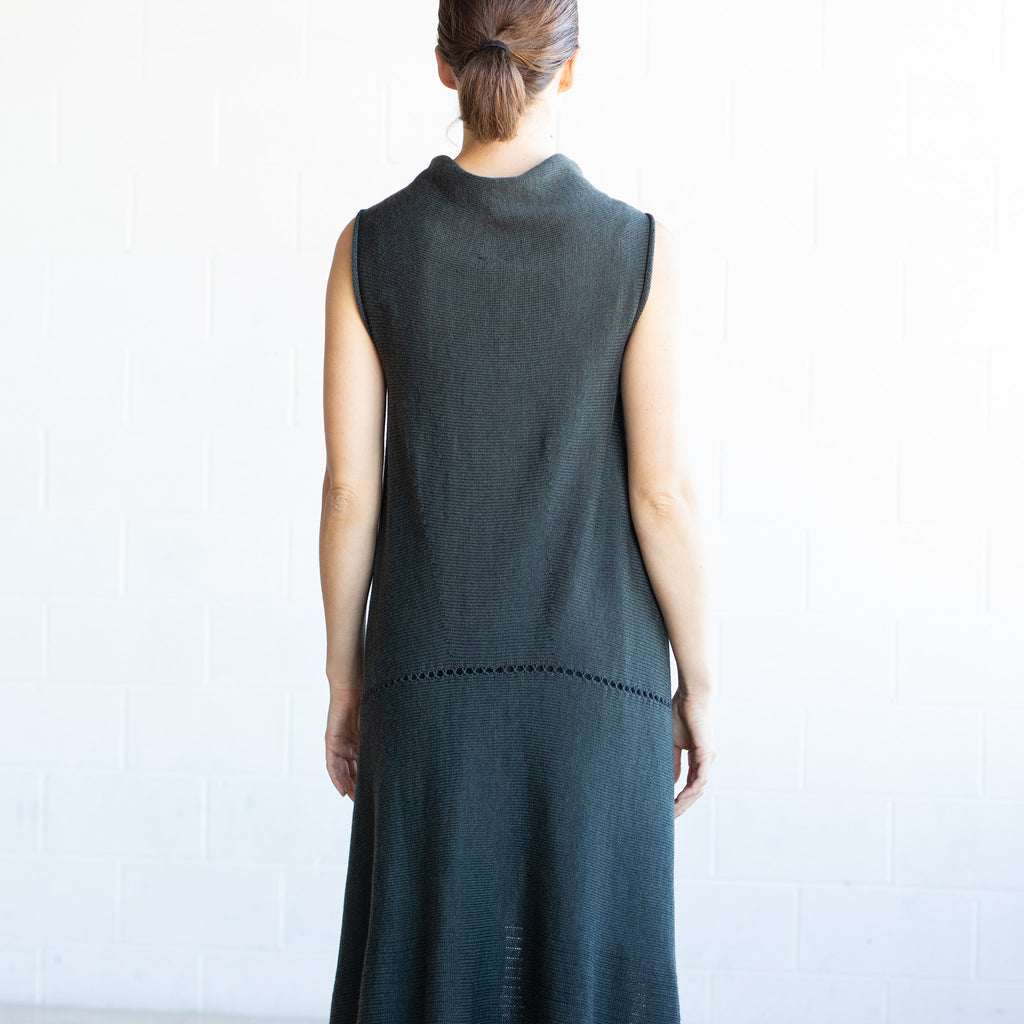 Back view of Asymmetric Longline vest design by Wendy Voon knits in deep forest green merino, with seam and stitch detail