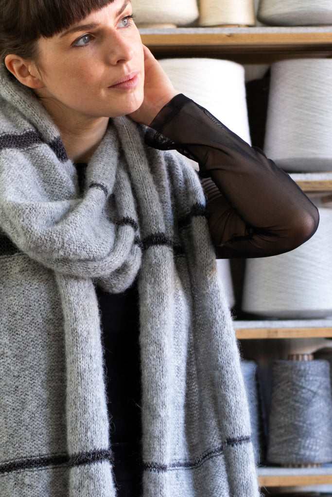 Close up view of alpaca striped wrap designed by Wendy Voon knits in silver grey alpaca with eggplant linen stripes