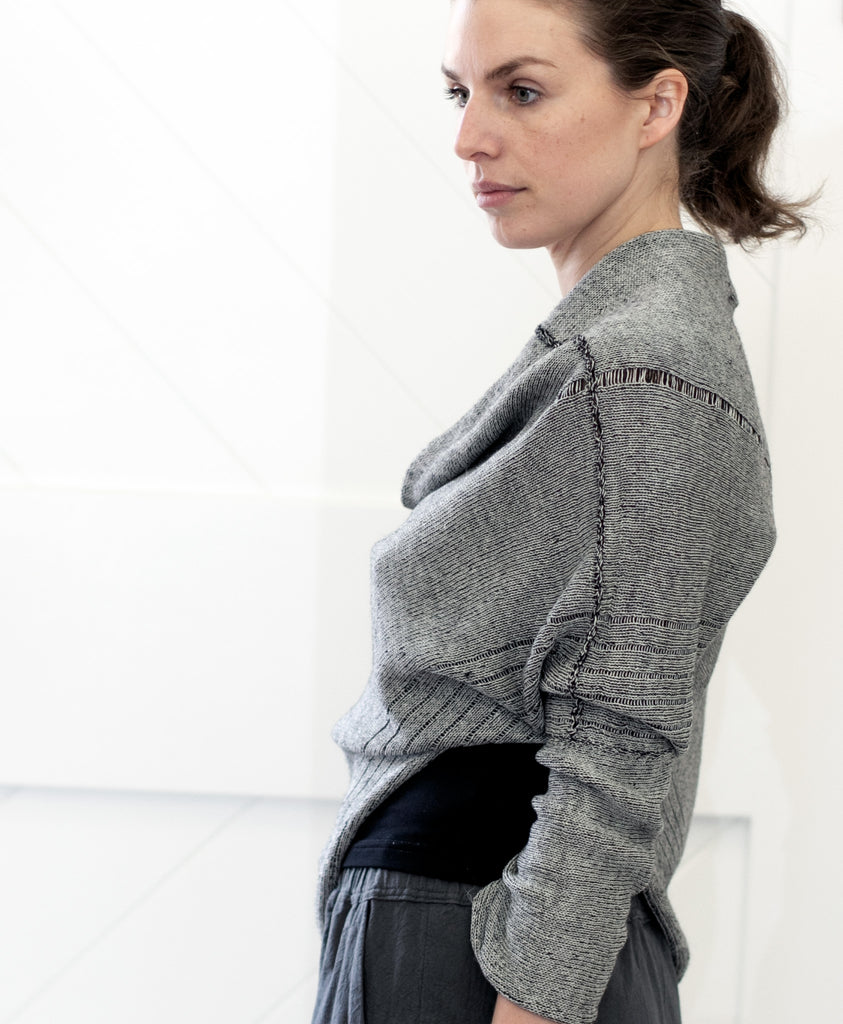 Side front view of Bias Jumper design by Wendy Voon knits in silver grey linen backed with black merino wool