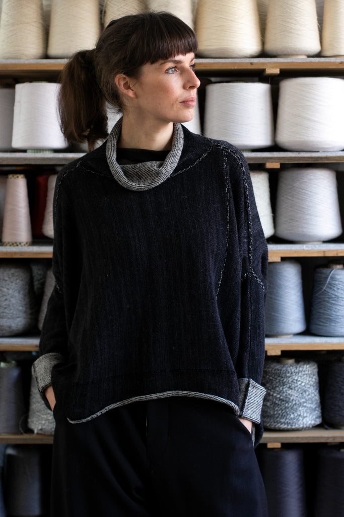 Front view of reversible box shaped jumper designed by Wendy Voon, made from superfine merino wool, with black colourway showing.