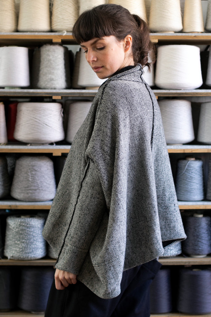 Side view of reversible box shaped jumper designed by Wendy Voon, made from superfine merino wool, with cream colourway showing.