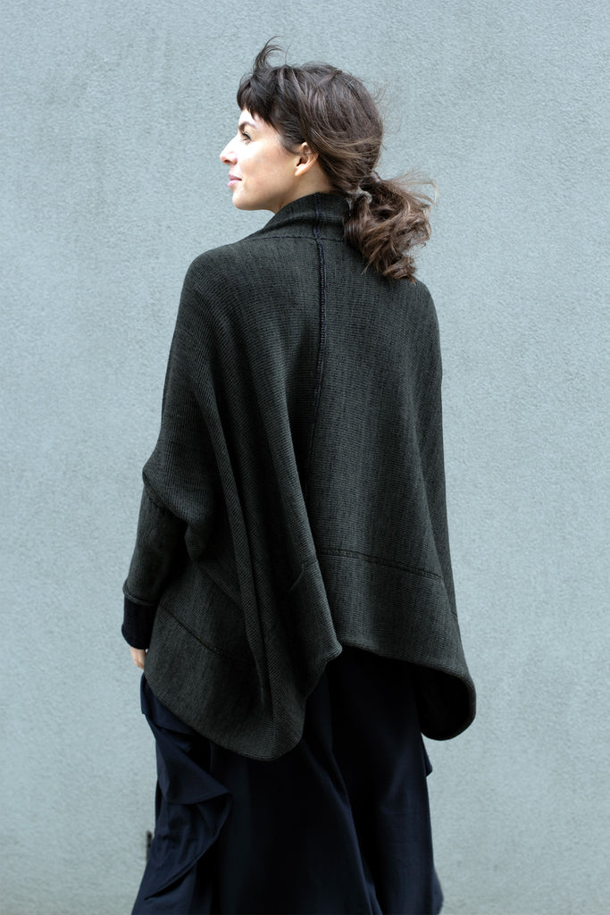 Back view of box shaped jumper designed by Wendy Voon, in an olive with charcoal/black backed fabric, made from superfine merino wool.