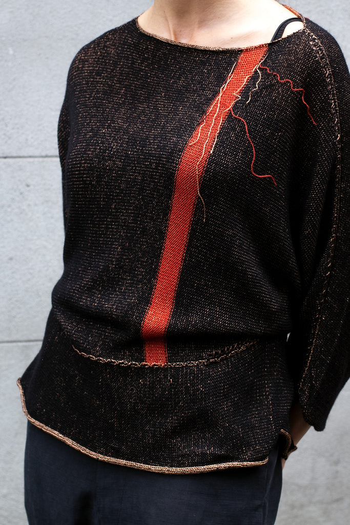 Detail view of Single Stripe Dolman Jumper design by Wendy Voon in black merino with peach viscose reverse and rust stripe