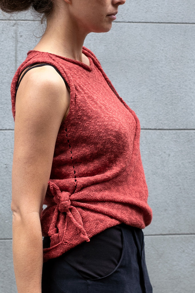 Side view of Double Up Top design by Wendy Voon knits in coral linen cotton, loop worn long and knot side detail