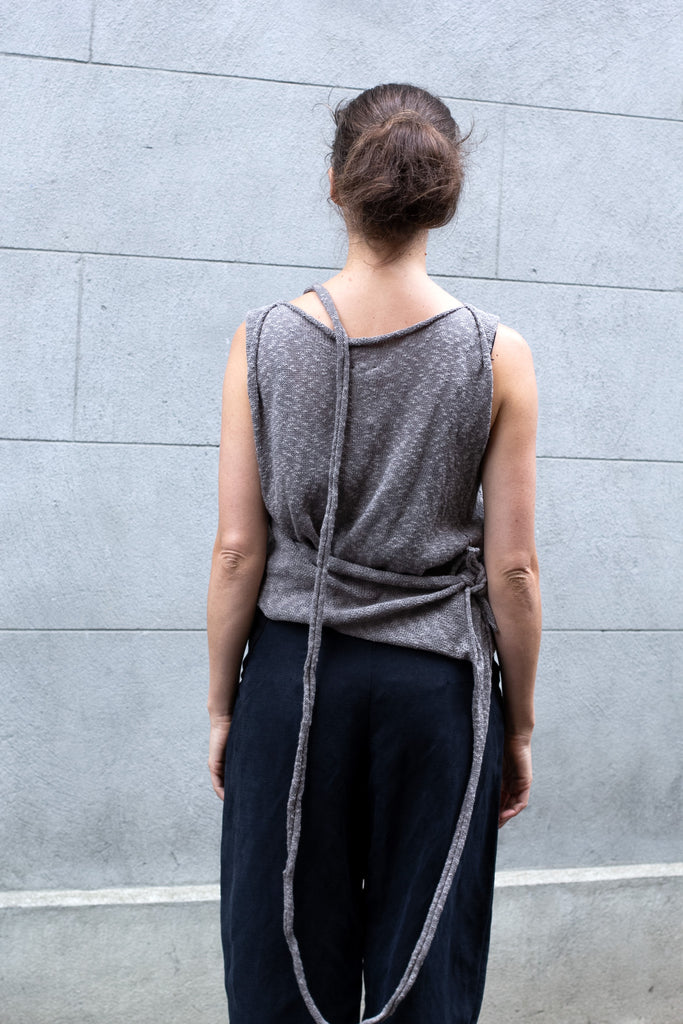 Back view of Double Up Top design by Wendy Voon knits in taupe linen cotton, loop worn long and side knot detail