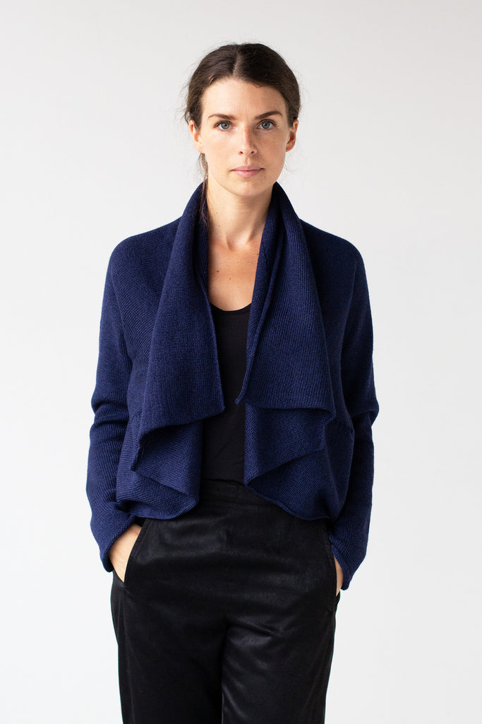 Front view of Shawl Collared Cardigan design by Wendy Voon knits in blue melange merino wool, worn short bolero style
