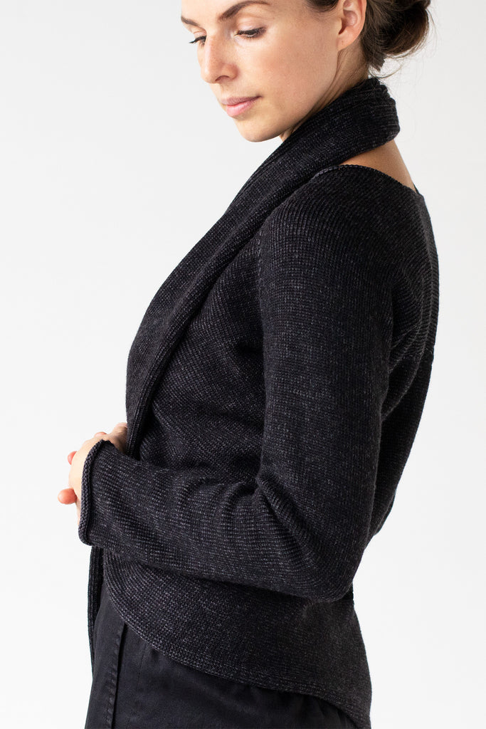 Side detail view of the Merino Cross Over, shown in charcoal and black fleck worn with front looped around the neck as a cardigan
