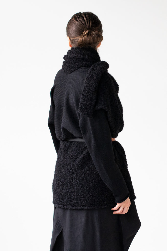 Side back view of Logical Progression Coat by Wendy Voon in black merino and alpaca, worn short and belted at waist