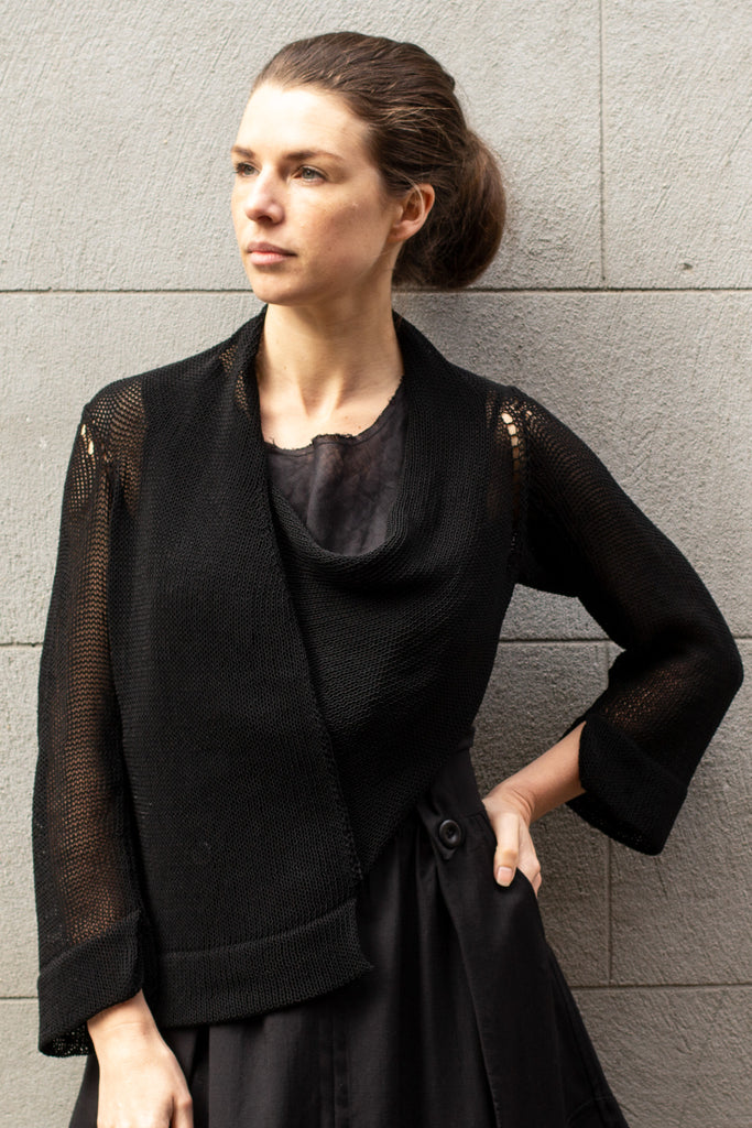 Front view of Cropped Viscose Jumper design by Wendy Voon knits in black, showing asymmetric hem and cowl neck details