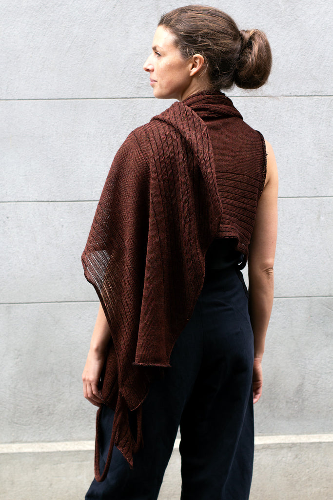 Back view of Multi-Wrap in Linen by Wendy Voon knits in rust linen with black reverse side, worn as cropped shawl style wrap