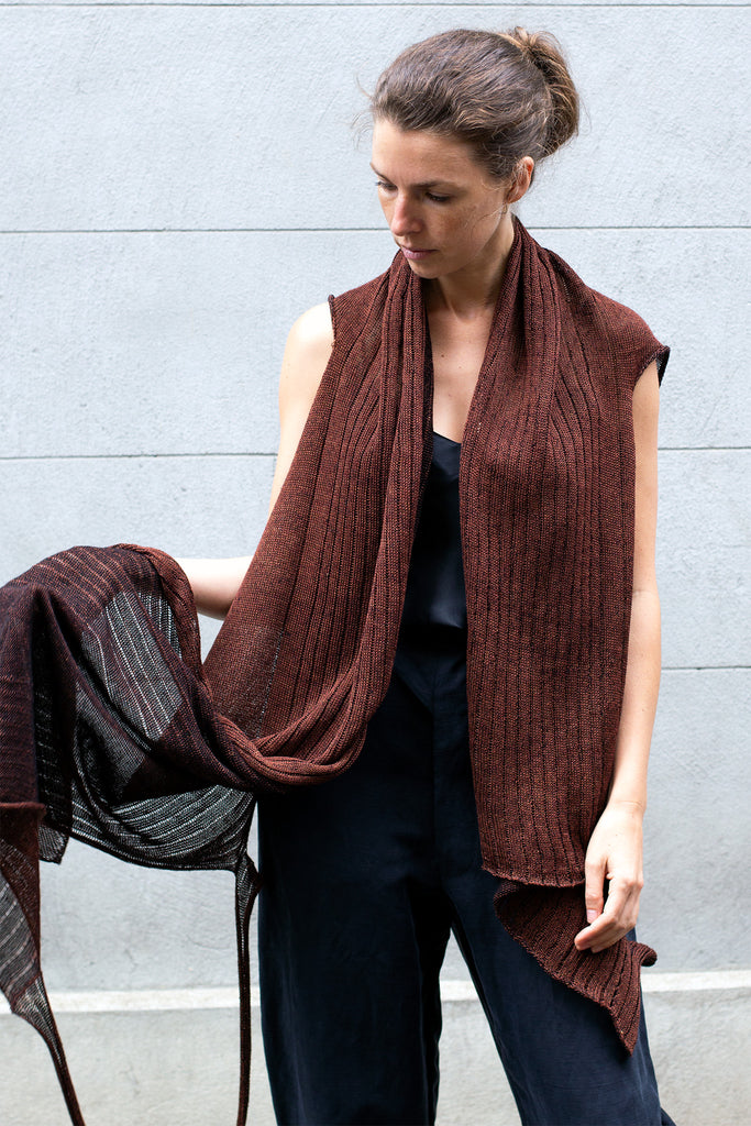 Front view of Multi-Wrap in Linen by Wendy Voon knits in rust linen with black reverse side, worn as cropped open style wrap