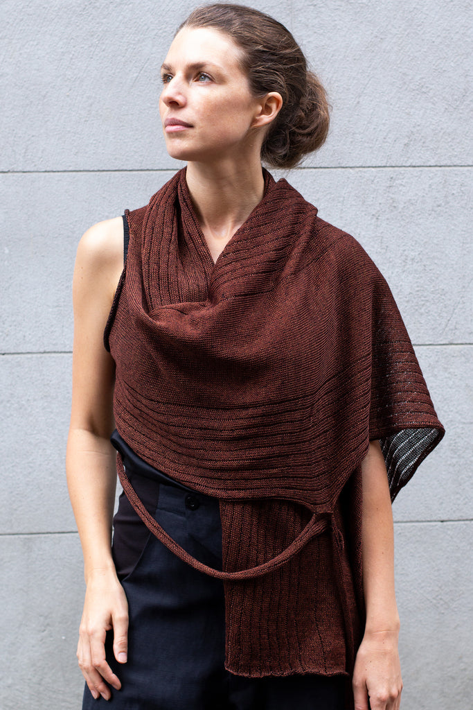 Front view of Multi-Wrap in Linen by Wendy Voon knits in rust linen with black reverse side, worn as cropped shawl style wrap