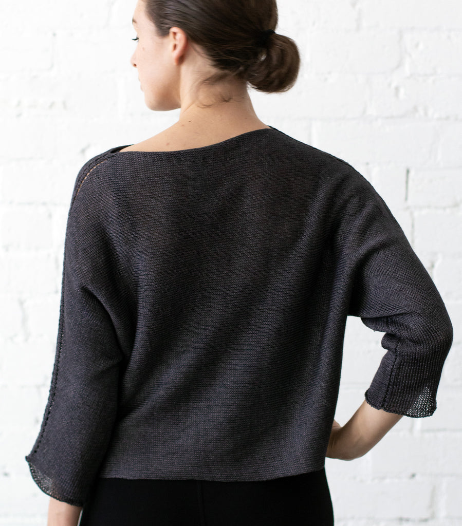 Back view of Linen Batwing jumper design by Wendy Voon knits in charred eggplant linen, showing batwing silhouette
