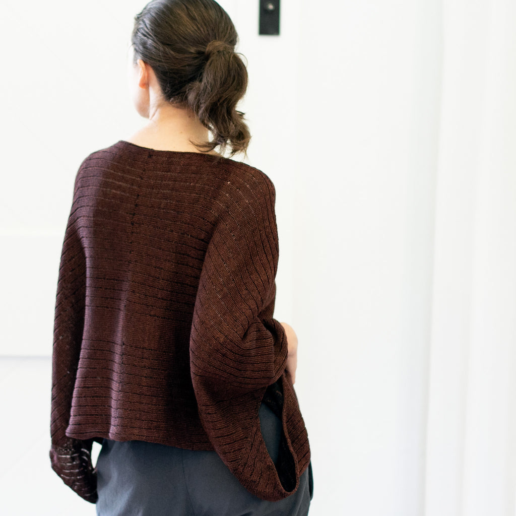 Back view of Linen Poncho design by Wendy Voon knits in rust linen cotton backed with black merino wool