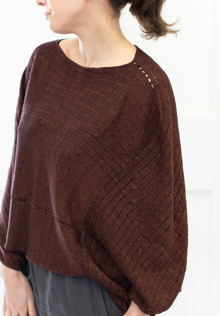Front view of Linen Poncho design by Wendy Voon in rust linen cotton backed with black merino wool, showing shoulder seam detail