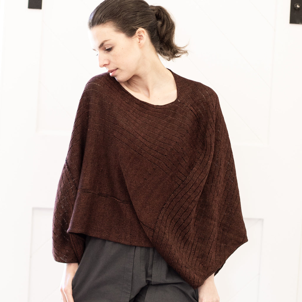 Front view of Linen Poncho design by Wendy Voon knits in rust linen cotton backed with black merino wool
