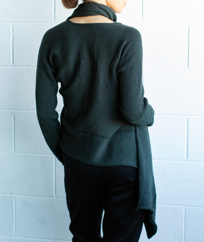 Back view of the Merino Cross Over by Wendy Voon in deep forest green, worn with front looped as a closed asymmetric cardigan