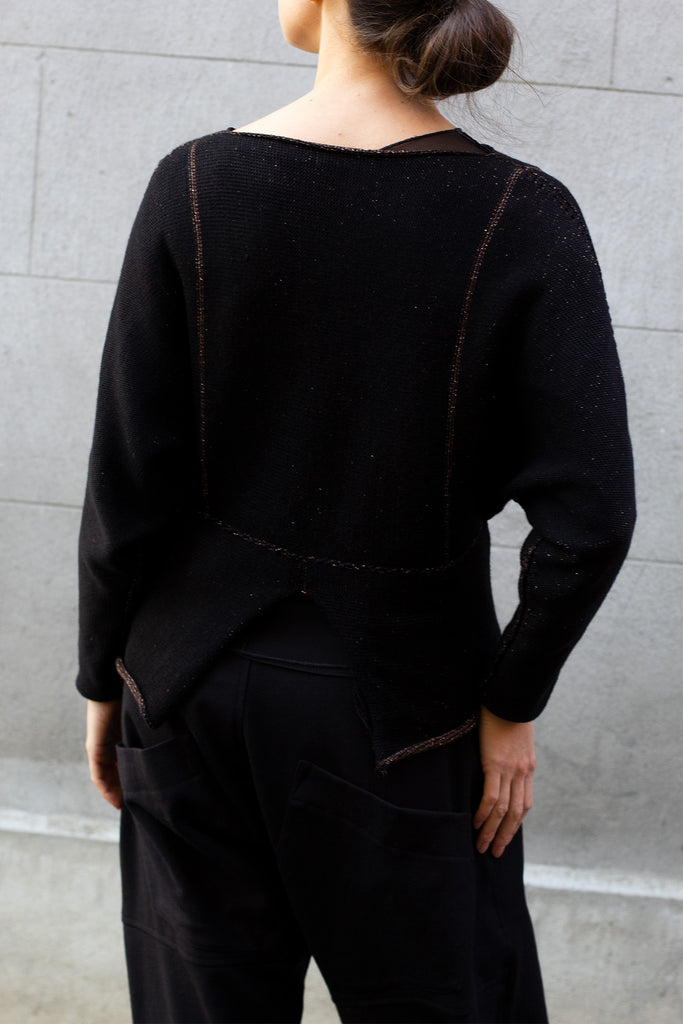 Back of metallic dolmain jumper with black side showing