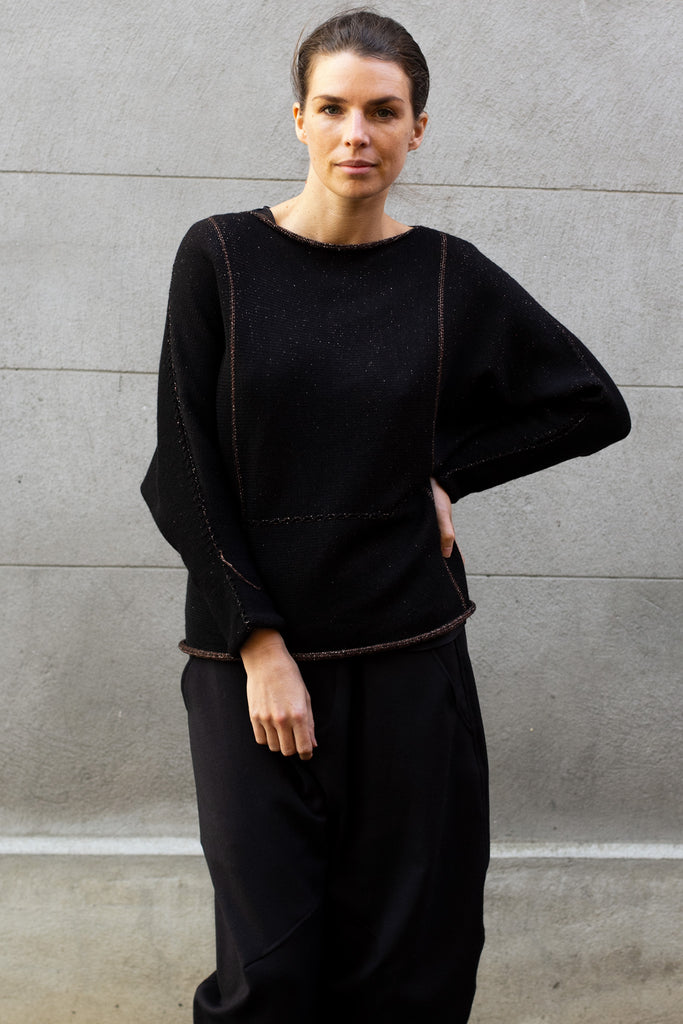 Front of metallic dolmain jumper with black side showing