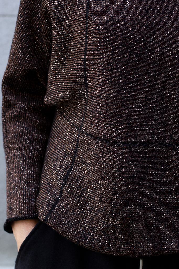 Detail of metallic dolmain jumper fabric with brown gold side showing
