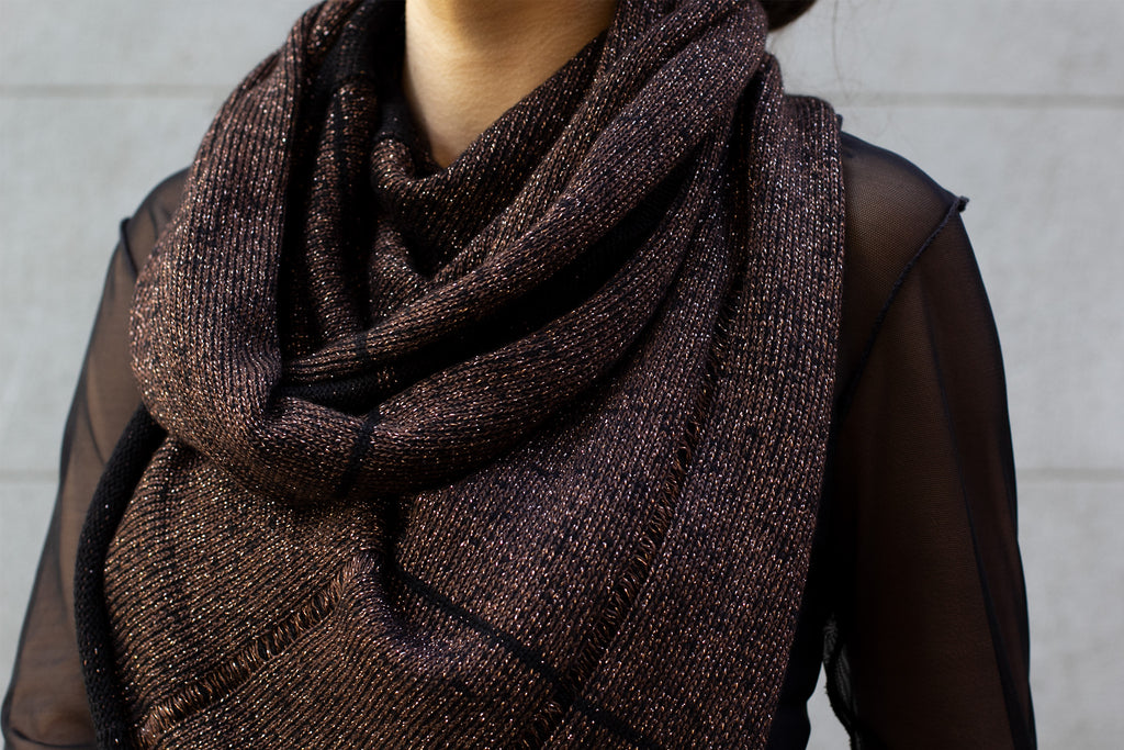 Close up of two toned metallic scarf fabric in black and brown gold