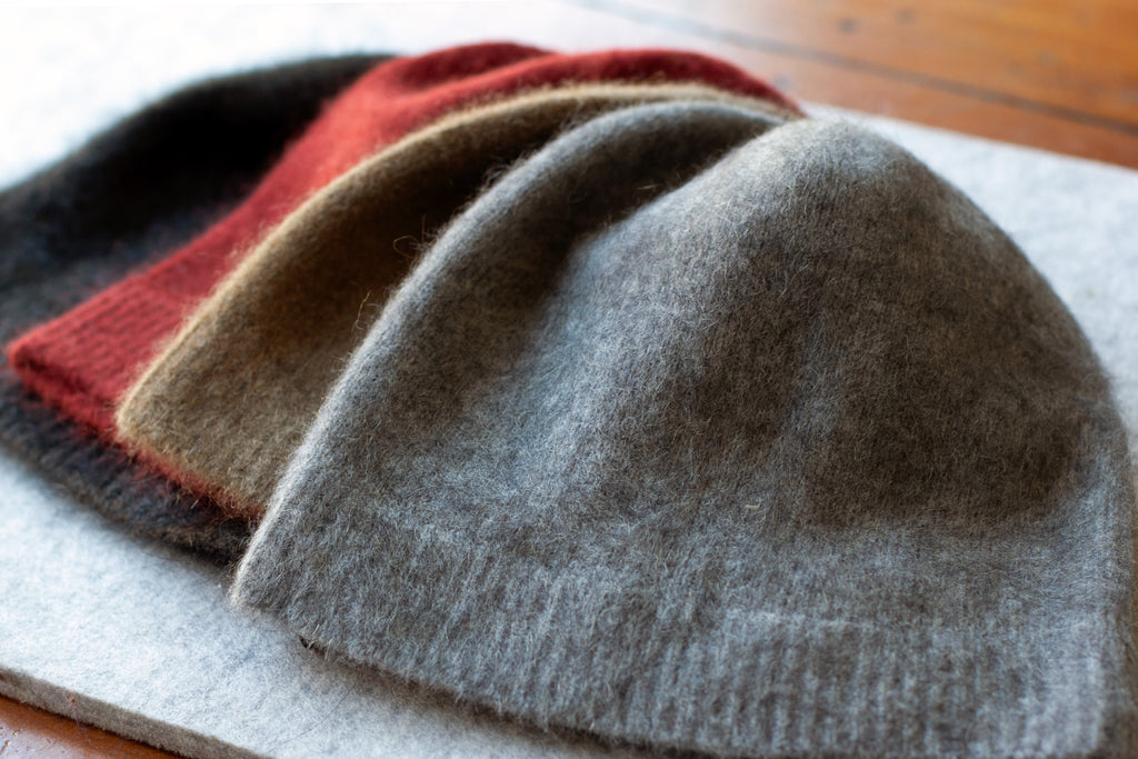 Group of coloured knitted beanie made from merino wool, possum and silk. Colours are dark tawny, burnt red, camel and light grey