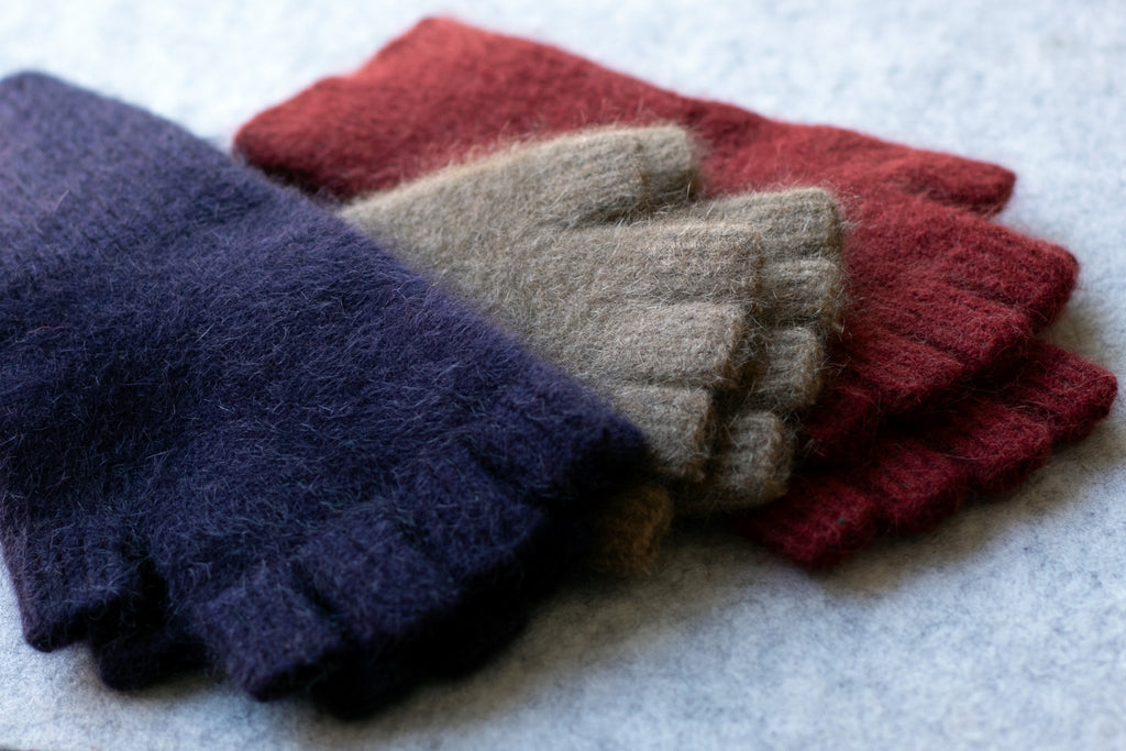 Group of coloured fingerless gloves in a merino wool, possum and silk blend. Colours are Aubergine, camel and red