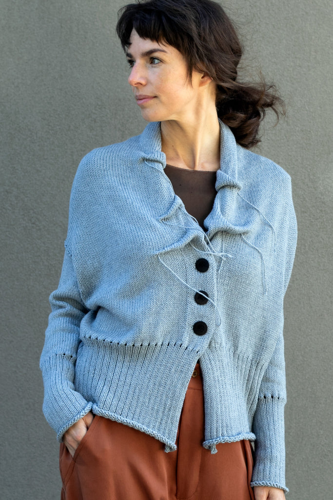 Front view of Ruched Chunky Knit Cardigan design by Wendy Voon in light blue cotton cashmere blend with black buttons worn closed