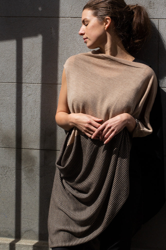 Front view of Striped Wrap design by Wendy Voon knits in black and oatmeal merino wool, worn as asymmetric poncho
