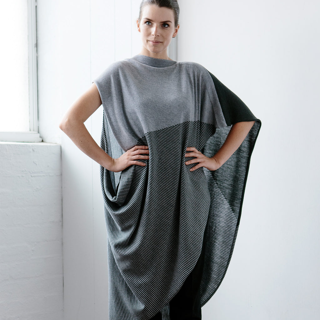 Front view of Striped Wrap design by Wendy Voon knits in grey and deep forest merino wool, worn as asymmetric poncho