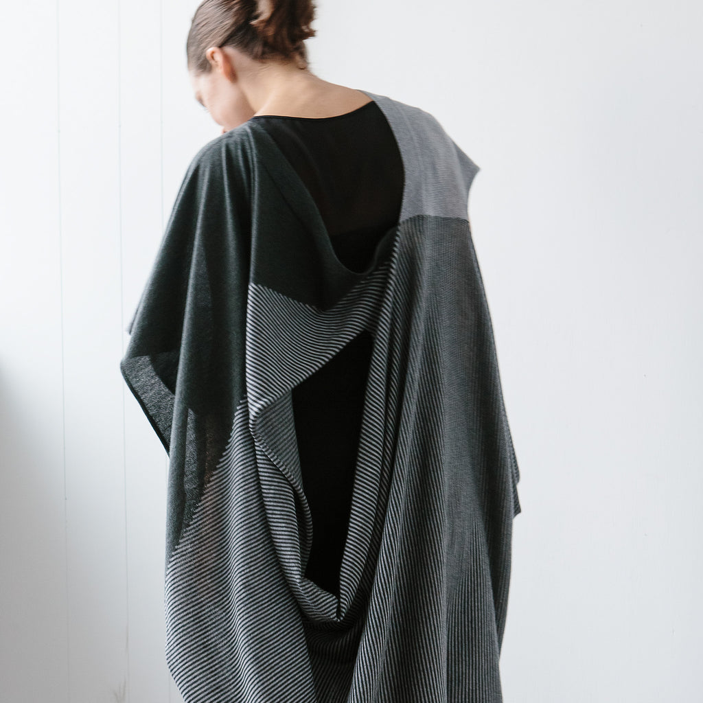 Back view of Striped Wrap design by Wendy Voon knits in grey and deep forest merino wool, worn as asymmetric poncho