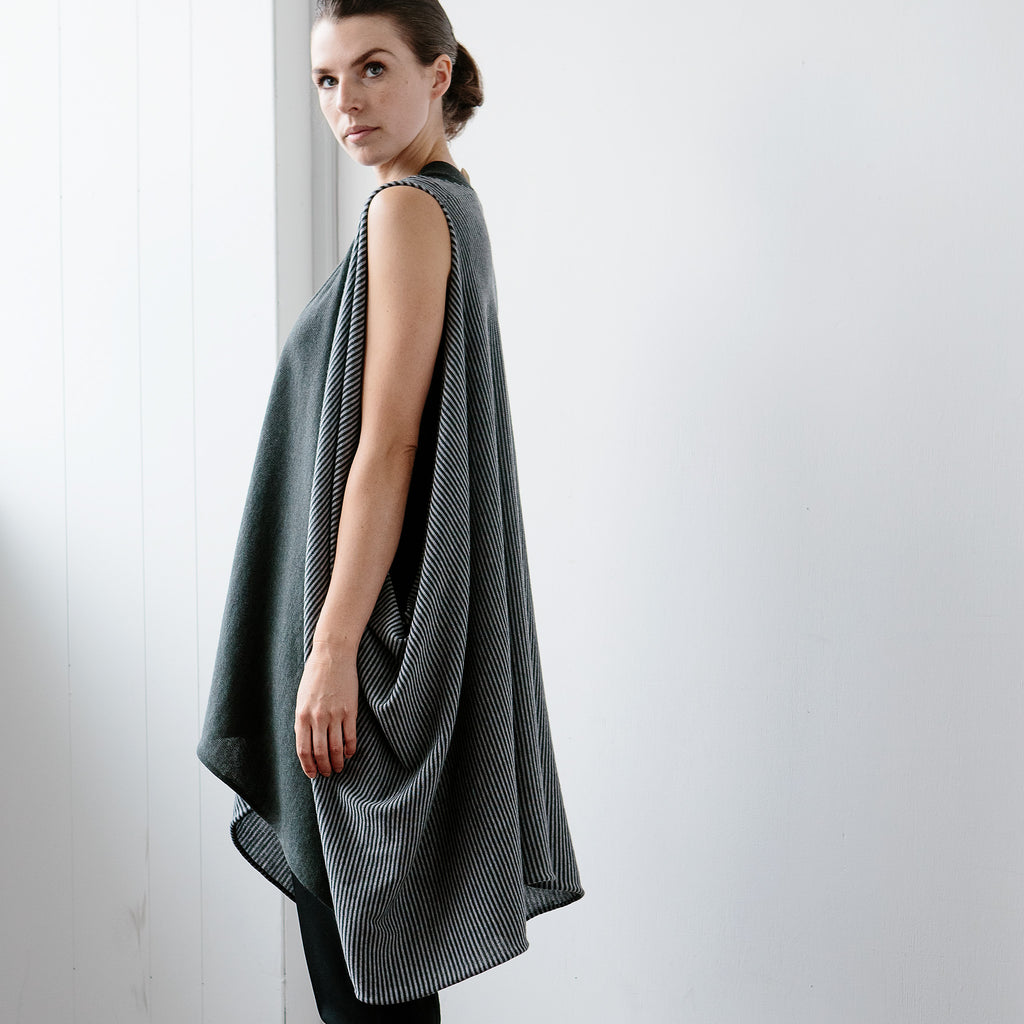 Side view of Striped Wrap design by Wendy Voon knits in grey and deep forest merino wool, worn as v neck, long loose vest