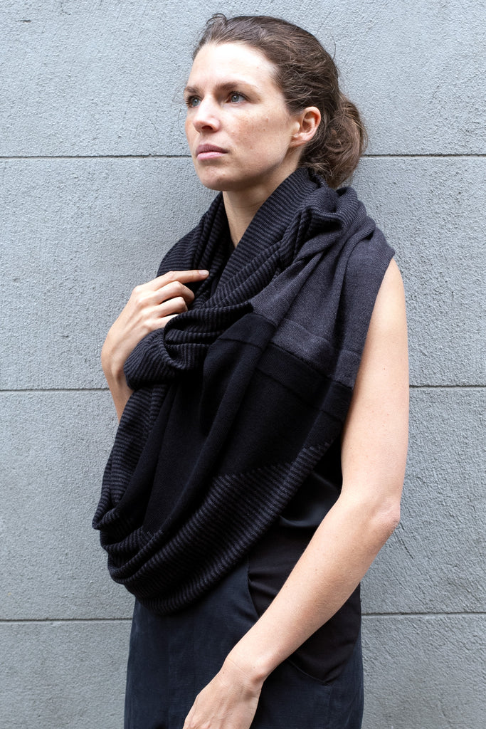 Front view of Striped Wrap design by Wendy Voon knits in black and charcoal merino wool, worn as scarf