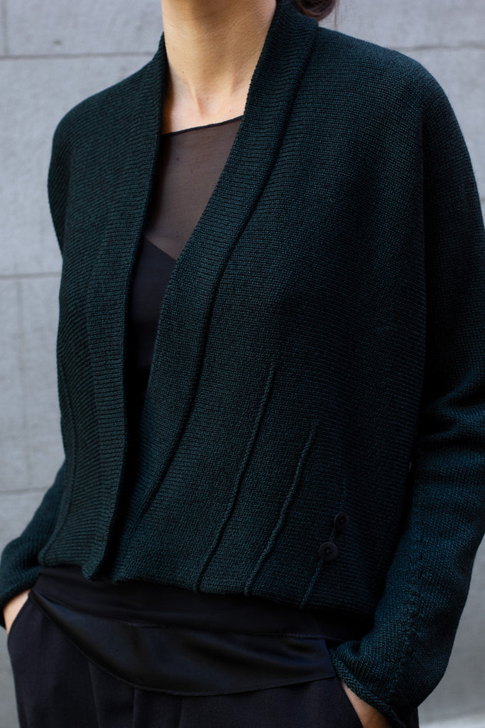 Front view of welted wool cardigan buttoned in emerald melange colourway