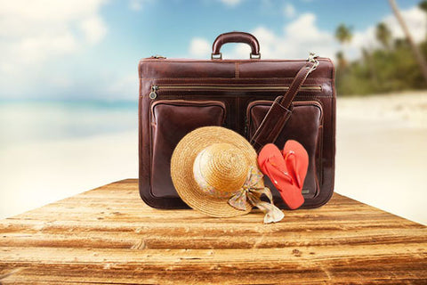 The Leather Garment Bag Sitting On The Beach With A Hat On Nice Sunny Day