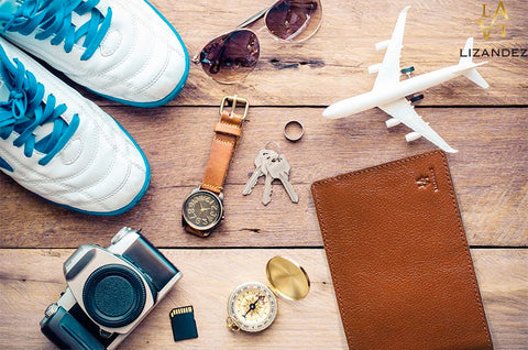 Leather Passport Wallet being Displayed On A table With Model Aeroplane. Watch, Sneakers Camera And Accessories