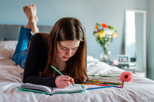 Teen girl alone in her room writing in a journal.