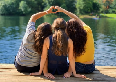 Three happy girls making a heart by the lake on a beautiful day.