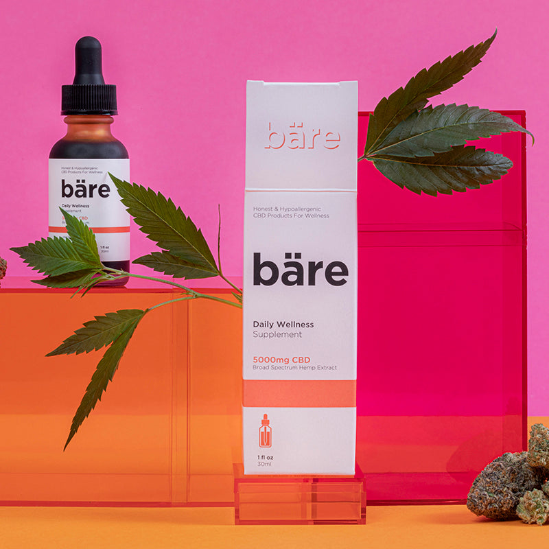 Kush Queen Bare CBD Tincture sitting on orange and pink boxes alongside cannabis plant leaves and nuggs.